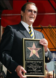 Roger Moore shows off his star on the Hollywood walk of fame